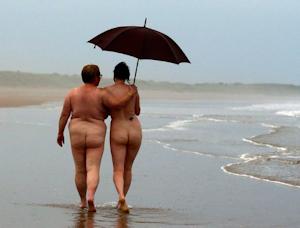 Deux libertins bras dessus bras dessous déambulent sur la plage sous un parapluie